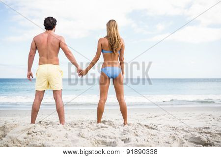 Happy couple holding hands and looking at the sea at the beach
