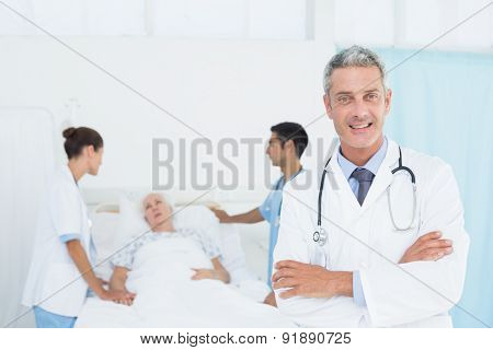 Portrait of female doctor with colleagues and patient behind