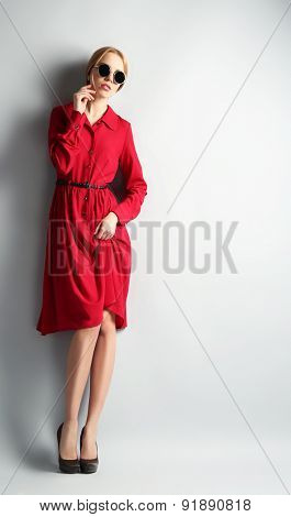 Expressive young model in red dress and sunglasses on gray background