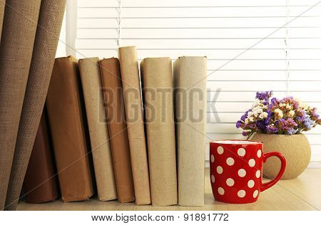 Books, cup and plant on wooden windowsill, closeup
