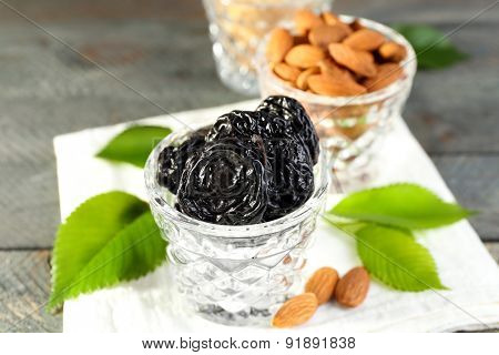 Prunes and almonds in glasses with leaves on wooden table, closeup