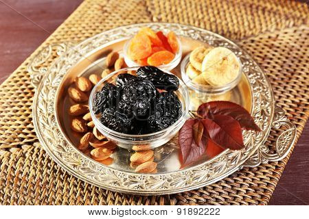 Prunes and other dried fruits with grape leaves on wicker mat, closeup