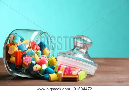 Colorful candies in jar on table on blue background