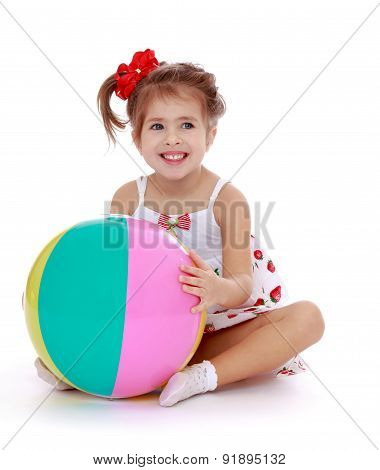 The girl sitting on the beach hugging a large striped ball