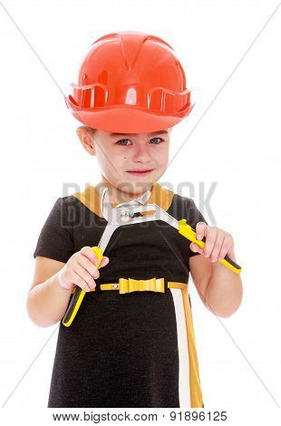 Funny little girl with a pair of pliers in his hands