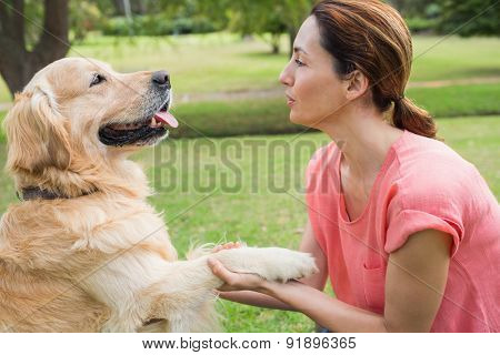 Pretty brunette playing with her dog in the park on a sunny day