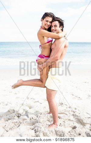 Happy couple hugging and looking at camera at the beach