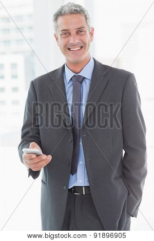 happy business man using smartphone in office