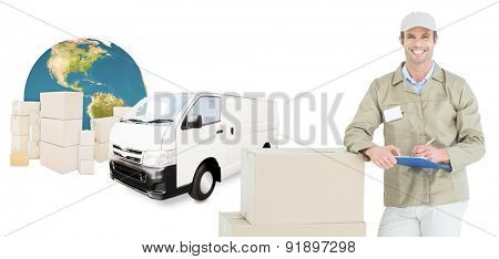 Happy delivery man writing on clipboard by cardboard boxes against logistics graphic