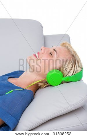 Happy woman listening music on the couch on white background