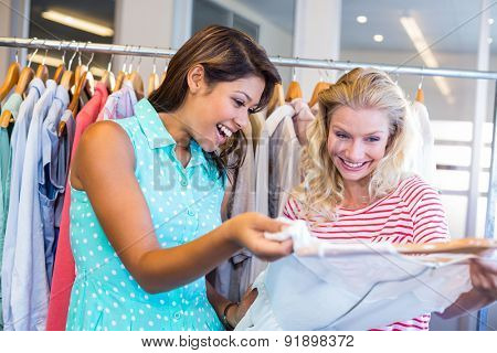Smiling friends doing shopping together in clothes store