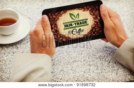 Businessman holding small tablet at table against fair trade