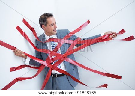 Businessman trapped by red tape on white background