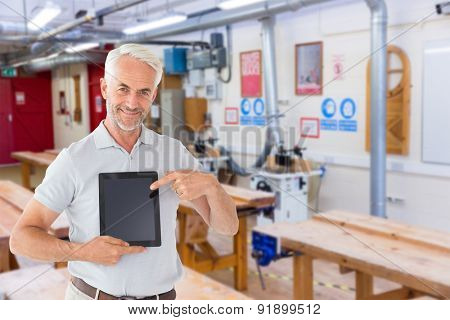 Mature student showing tablet pc against workshop