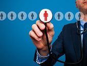 picture of recruitment  - Businessman hand with stethoscope - JPG