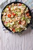 picture of caesar salad  - Caesar salad with shrimps on a black plate - JPG