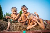 foto of hay bale  - boys sitting on a hay bale on sky background - JPG
