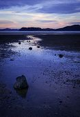 stock photo of tide  - The outgoing tide reveals mudflats that reflect the evening sky - JPG