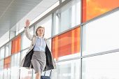 picture of carry-on luggage  - Young businesswoman with luggage running in railroad station - JPG