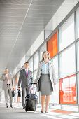 image of carry-on luggage  - Full length of businesspeople with luggage walking in railroad station - JPG