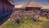stock photo of abandoned house  - the remains of wooden carts on the background of abandoned wooden houses - JPG