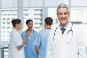 stock photo of medical office  - Portrait of a smiling confident male doctor at medical office - JPG