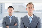 picture of frown  - Two businessmen frowning at camera in the office - JPG