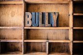 image of self-torture  - The word BULLY written in vintage wooden letterpress type in a wooden type drawer - JPG