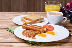 picture of british culture  - Traditional English breakfast with sausage fried eggs beans coffee and orange juice - JPG