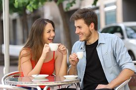 stock photo of flirt  - Happy couple or friends flirting talking and drinking in a restaurant terrace - JPG