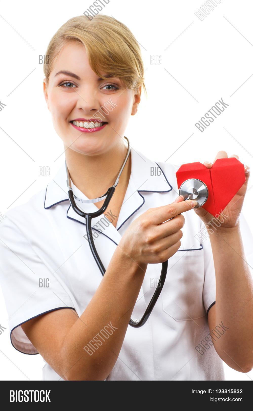 White apron health - Smiling Woman Doctor Cardiologist In White Apron With Stethoscope Examining Red Heart Of Paper Healthcare And