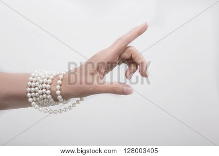Expensive beads represented on hand. Fashionable hand of woman showing white beads isolated on white background.
