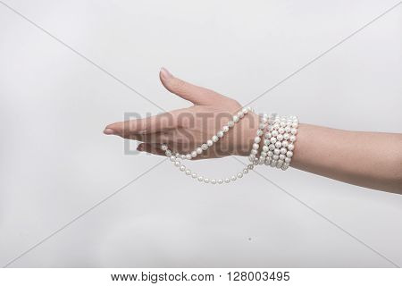 Expensive beads are on woman's hand isolated on white background. White beads represented by senior woman in studio.