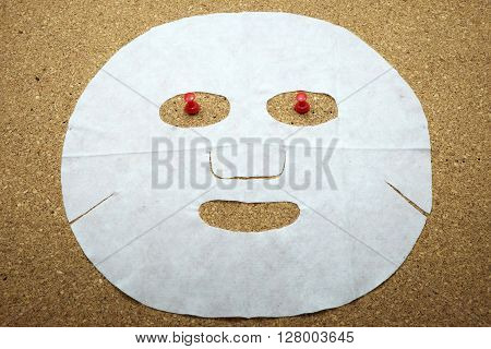 Facial mask with red push pins on cork message board/bulletin board.