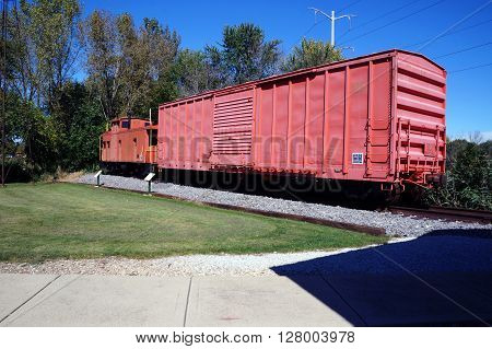 PLAINFIELD, ILLINOIS / UNITED STATES - SEPTEMBER 20, 2015: An old boxcar and caboose of the former Elgin, Joliet and Eastern (EJ&E) Railway sits on a railroad track in Plainfield.