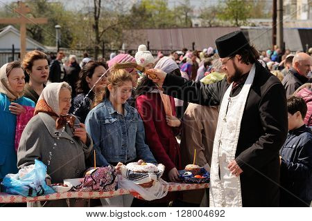 Orel Russia - April 30 2016: Paschal blessing of Easter baskets in Orthodox church. Priest pouring holy water on crowd of people horizontal