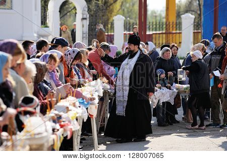 Orel Russia - April 30 2016: Paschal blessing of Easter baskets in Orthodox church. Priest sprinkling holy water on people and kulichi in Bogoyavlenskaya church yard horizontal