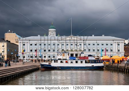 HELSINKI, FINLAND - APRIL 23, 2016: Floating cafe in harbor near Market Square (Kolera-allas; Cholera Basin). On the background is City Hall Building and the Helsinki Cathedral Dome