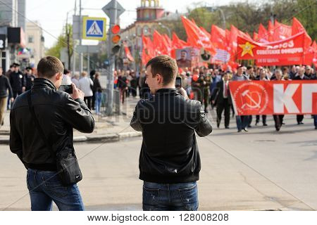 Orel Russia - May 1 2016: Communist party demonstration. Young mens shooting people with red flags closeup