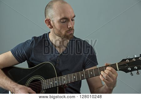 Young guitarist playing his acoustic guitar close up
