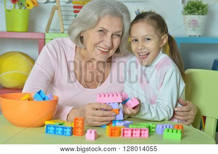 Portrait of a happy grandmother with granddaughter playing together