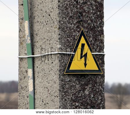 Reinforced concrete electricity pole with sign warning caution electricity shock risk high voltage keep out hazard