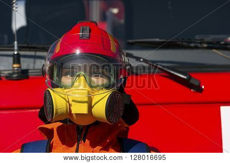 Firefighter hard hat, breathing mask or respirator with interchangeable filter cartridges and safety goggles on mannequin with red fire-fighting truck on background, fireman protective means, rescue service