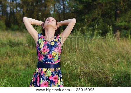 Beautiful young woman standing in a forest clearing with closed his eyes enjoying the warm rays of the summer sun