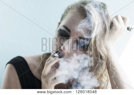 Portrait of young pretty pensive young woman smoking