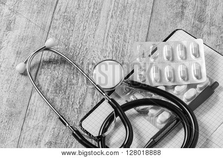 stethoskope on wooden desk with pills pencil and notebook copy space B/W