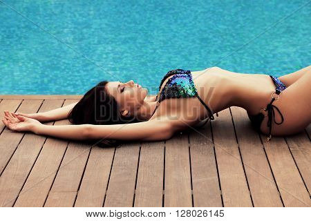 fashion outdoor photo of gorgeous woman with dark hair in elegant swimsuit posing beside swimming pool