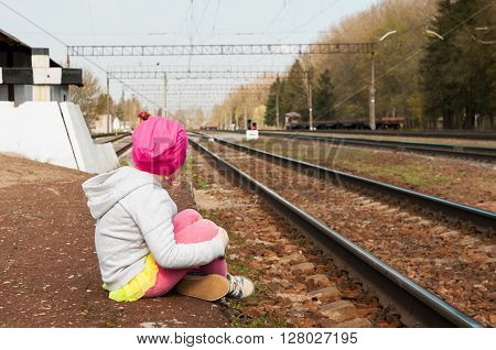 lonely little girl sitting on a railway platform