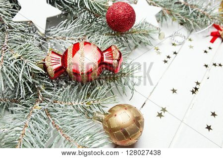 Christmas or New Year decoration background: fur-tree branches, colorful glass balls, decoration and glittering stars on white wooden background, top view, copy space