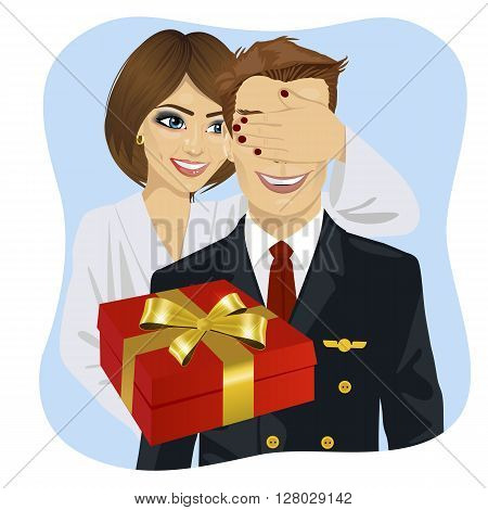 wife in white bathrobe covering her husband's eyes wearing airline pilot uniform standing behind him with gift on blue background